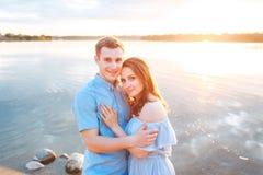 Jeunes beaux couples dans l'amour restant et embrassant sur la plage sur le coucher du soleil Couleurs ensoleillées douces Photos libres de droits