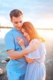 Jeunes beaux couples dans l'amour restant et embrassant sur la plage sur le coucher du soleil Couleurs ensoleillées douces Image libre de droits