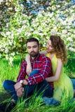 Jeunes beaux couples dans l'amour se reposant dans le jardin de floraison Photos stock