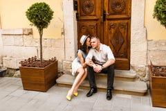 Jeunes beaux couples dans l'amour se reposant sur la vieille rue de ville Photos libres de droits