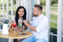 Jeunes beaux couples dans l'amour une date dans un café La fille sourit dans l'embarras, l'homme brutal l'alimente avec elle photos libres de droits
