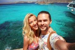 Jeunes beaux couples dans l'amour voyageant et faisant le selfie à partir de la roche de la lagune bleue à Malte, ayant l'amuseme Images libres de droits
