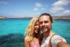 Jeunes beaux couples dans l'amour voyageant et faisant le selfie à partir de la roche de la lagune bleue à Malte, une fille souri Photo libre de droits