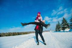 Jeunes beaux couples dans l'amusement lumineux d'hiver de vêtements dans la neige, mode de vie, vacances d'hiver Photographie stock