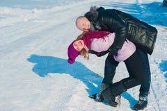 Jeunes beaux couples dans l'amusement lumineux d'hiver de vêtements dans la neige, mode de vie, vacances d'hiver Photographie stock libre de droits