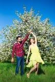 Jeunes beaux couples dans la danse d'amour dans le jardin de floraison Photos stock