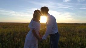 Jeunes beaux couples dans un domaine de blé Silhouette sur le fond de coucher du soleil Mouvement lent Images stock