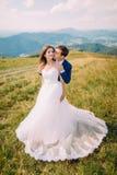 Jeunes beaux couples de mariage posant sur le champ d'herbe ensoleillé avec Forest Hills éloigné et ciel merveilleux comme fond Photographie stock libre de droits