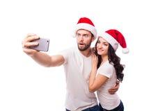 Jeunes beaux couples de Noël dans des chapeaux de Santa dans l'amour prenant l'autoportrait romantique Image stock
