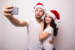 Jeunes beaux couples de Noël dans des chapeaux de Santa dans l'amour prenant l'autoportrait romantique Image libre de droits