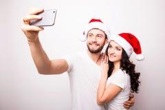 Jeunes beaux couples de Noël dans des chapeaux de Santa dans l'amour prenant l'autoportrait romantique Photographie stock