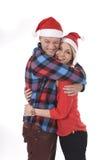 Jeunes beaux couples de Noël dans des chapeaux de Santa dans le sourire d'amour heureux ensemble s'étreignant doux Photos stock