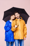 Jeunes beaux couples doux posant dans des manteaux de pluie tenant le parapluie au-dessus du fond rose-clair Photographie stock