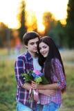 Jeunes beaux couples embrassant et souriant au coucher du soleil en été Image stock