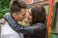 Jeunes beaux couples embrassant sur le fond de l'autobus hippie de razrisovanogo tout en marchant à Lviv en filmant l'histoire d' Photographie stock
