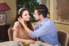 Jeunes beaux couples enamourés se reposant à une table dans un café Photos libres de droits