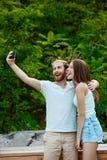 Jeunes beaux couples faisant le selfie, souriant, marchant en parc Fond extérieur Images stock