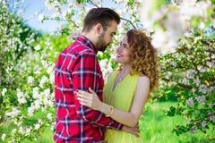 Jeunes beaux couples heureux dans l'amour posant dans le jardin de floraison Images libres de droits