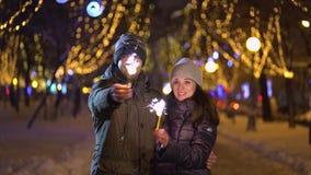 Jeunes beaux couples heureux de sourire tenant des étincelles clips vidéos