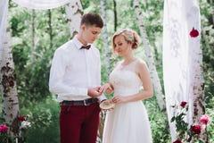 Jeunes beaux couples, jeunes mariés dans la forêt dans la perspective du décor de mariage Images libres de droits