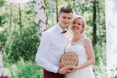 Jeunes beaux couples, jeunes mariés dans la forêt dans la perspective du décor de mariage Photographie stock