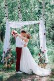 Jeunes beaux couples, jeunes mariés dans la forêt dans la perspective du décor de mariage Image libre de droits