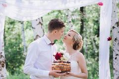 Jeunes beaux couples, jeunes mariés dans la forêt dans la perspective du décor de mariage Photo stock