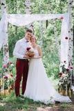 Jeunes beaux couples, jeunes mariés dans la forêt dans la perspective du décor de mariage Image stock