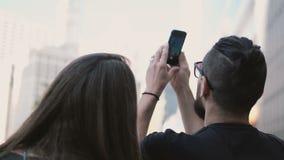 Jeunes beaux couples marchant dedans le centre ville de Chicago, Amérique et prenant la photo du gratte-ciel sur le smartphone banque de vidéos
