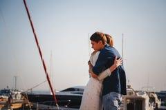 Jeunes beaux couples mignons étreignant au pilier au port avec de petits yachts, hippies Photographie stock libre de droits