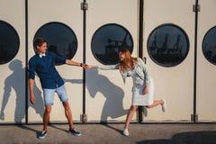 Jeunes beaux couples mignons badinant au port, sur le mur blanc avec le grand fond de hublots, portrait extérieur de sourire heur image stock