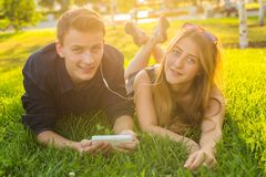 Jeunes beaux couples ou étudiants universitaires se couchant sur l'herbe ensemble, écoutant la musique Photographie stock libre de droits