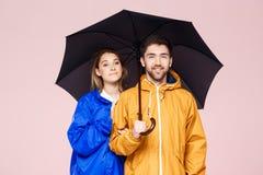 Jeunes beaux couples posant dans des manteaux de pluie tenant le parapluie au-dessus du fond rose-clair Photographie stock