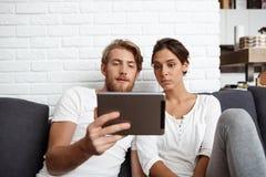 Jeunes beaux couples regardant le comprimé se reposant sur la maison de sofa photos libres de droits