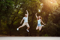 Jeunes beaux couples sautant, souriant, se réjouissant, marchant en parc Fond extérieur Photo libre de droits