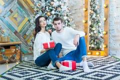 Jeunes beaux couples se reposant près de l'arbre de Noël avec le boxe de rouge de giftsin de Noël Images stock