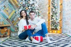 Jeunes beaux couples se reposant près de l'arbre de Noël avec le boxe de rouge de giftsin de Noël Photo stock