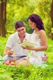 Jeunes beaux couples se reposant sur l'herbe en parc souriant et images libres de droits