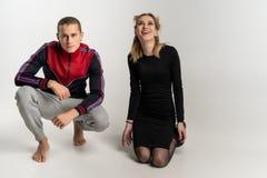 Jeunes beaux couples se reposant sur le plancher, portrait de studio photographie stock