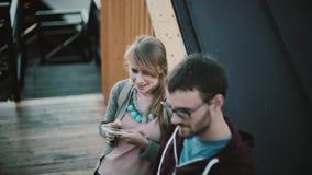Jeunes beaux couples se tenant au centre et à parler de la ville Participation heureuse de femme, utilisant le smartphone tenant  banque de vidéos
