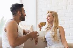 Jeunes beaux couples Sit On Coach Near Window, tasse de café de matin de boissons, homme de sourire heureux et femme hispaniques Photographie stock libre de droits