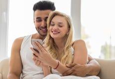 Jeunes beaux couples Sit On Coach Near Window, utilisant la femme hispanique d'homme de sourire heureux futé de téléphone de cell Photos stock