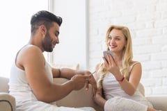 Jeunes beaux couples Sit On Coach Near Window, utilisant la femme hispanique d'homme de sourire heureux futé de téléphone de cell Photographie stock libre de droits