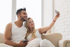 Jeunes beaux couples Sit On Coach Window, prenant la photo de Selfie sur le sourire heureux de téléphone intelligent de cellules Images libres de droits