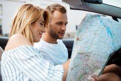 Jeunes beaux couples souriant, regardant la carte, se reposant dans la voiture Photographie stock