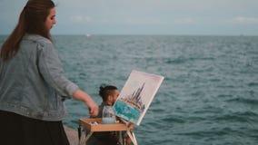 Jeunes beaux couples sur le rivage de la mer Femme créative dessinant la photo, homme jouant sur la guitare banque de vidéos