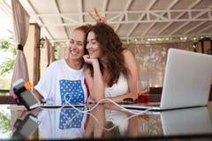 Jeunes beaux deux meilleurs amis de femmes se photographiant avec l'appareil-photo de téléphone portable par l'intermédiaire du b Photographie stock libre de droits