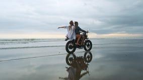 Jeunes beaux hippies de couples montant la r?tro moto sur la plage, le portrait ext?rieur, le type de monte et la fille, voyage banque de vidéos