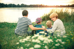 Jeunes beaux parents étreignant leurs jeunes fils au coucher du soleil près du lac Famille marchant le long de la rivière Image stock
