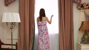 Jeunes beaux rideaux en ouverture de femme dans une chambre à coucher banque de vidéos